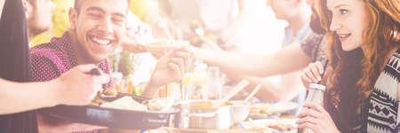 Junges Paar essen gesundes, Bio-Lebensmittel in einer Gesellschaft ihrer Freunde