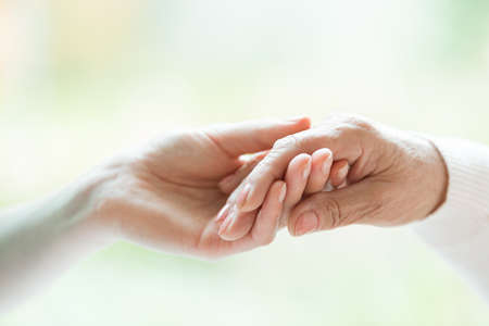 Close-up photo of young hand holding the older one