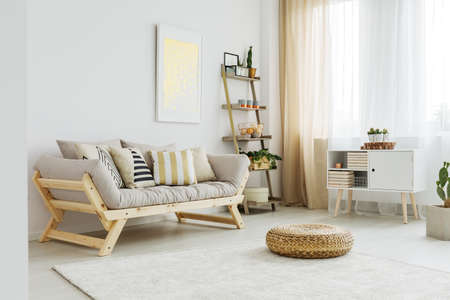 무늬 베개가있는 회색 소파 앞의 흰색 카펫에 소재 pouf 스톡 콘텐츠