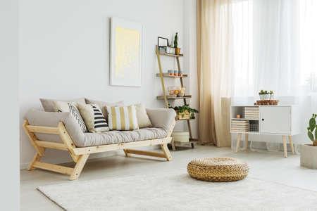 Materiële poef op wit tapijt voor grijze bank met gevormde kussens