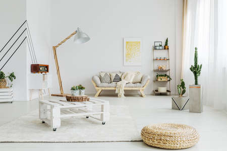 Designed, wooden table on wheels in living room with two cacti