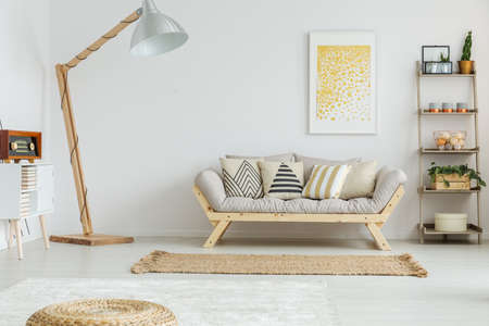 Ruime, witte woonkamer met comfortabele grijze bank en vintage decoraties