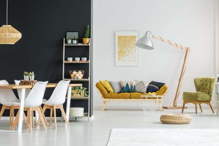 Plank met kaarsen, planten en ballen tegen zwarte muur in ruime loft