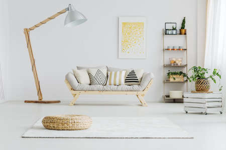 Grijze bank met gevormde kussens in lichte woonkamer met grote lamp Stockfoto