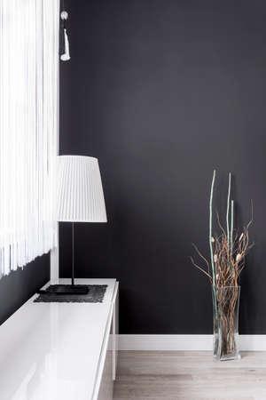 Eenvoudige lamp met witte lampscherm in zwarte kamer