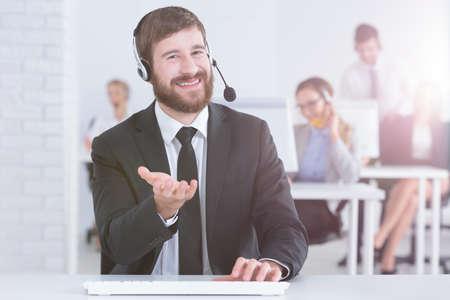 Jonge man in een pak werken als medewerker van de klantenservice Stockfoto