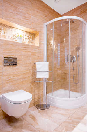 Douche dans la salle de bain moderne avec marbre beige et sculpture sur le mur