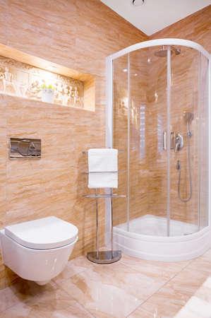 Douche in moderne badkamer met beige marmer en beeldhouwwerk aan de muur