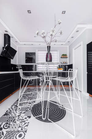 Trendy dining space with metal openwork chairs and table in modern black and white kitchen