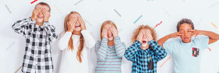 Group of children in casual clothes covering their eyes with their hands