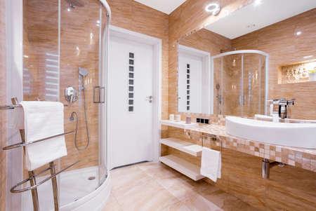 샤워 및 사암 타일이 달린 베이지 색 고급 욕실 스톡 콘텐츠 - 84520174
