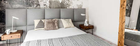 Fur pillow on bed with grey blanket in modern stylish bedroom with two white lamps