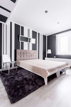 Fancy bed with tufted velvet headboard in modern room with fur carpet