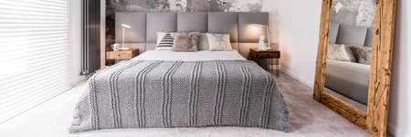 bedside: Front view of king-size bed with grey coverlet between two wooden bedside tables Stock Photo