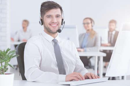 현대 사무실에서 잘 생긴 고객 서비스 컨설턴트 웃고