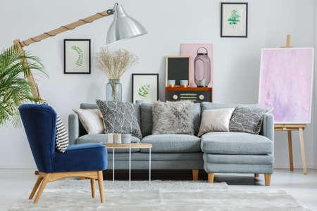 Gedessineerde kussens op grijze bankstel in woonkamer met vintage meubels en roze schilderij op ezel Stockfoto