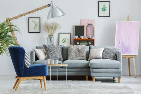 Patterned pillows on grey couch set in living room with vintage furnishings and pink painting on easel