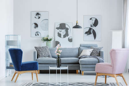 グレーのソファーと小さなコーヒー テーブルの上に黒い花瓶の居心地の良いリビング ルームでピンクとブルーのアームチェア 写真素材