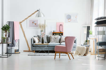 Grijze bank met decoratieve hoofdkussens in woonkamer met roze leunstoel en vintage radio