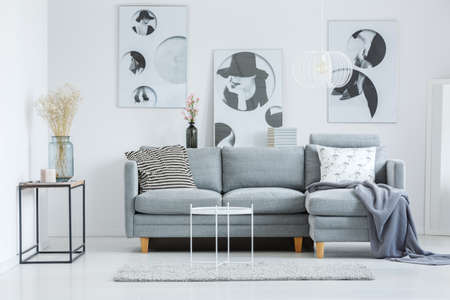 Glass vase on shelf near grey sofa with patterned pillows in fashionable living room with grey carpet