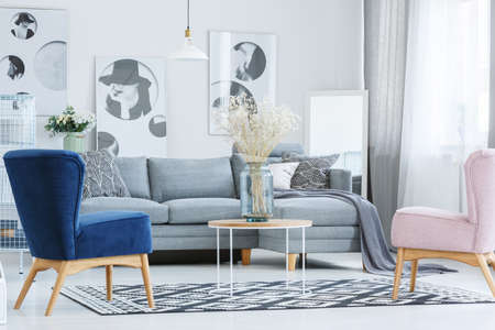 Glass vase with flowers on coffee table in stylish living room with designer armchairs and grey sofa Foto de archivo