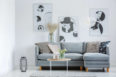 White designer lamp above grey settee and yellow flowers in vase on coffee table in living room with classic posters