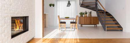 나무와 금속 계단이있는 흰색 넓은 식당 스톡 콘텐츠