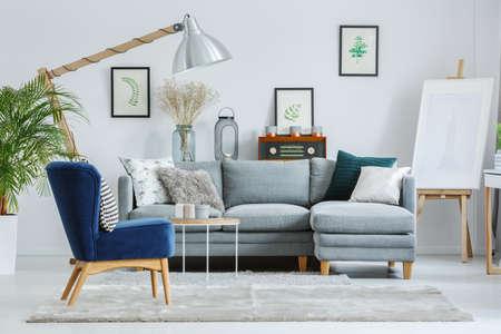 デザイナーズ リビング ルーム ランプ、イーゼルやグレーのソファでグレーのカーペットの上に青い椅子 写真素材 - 84587767