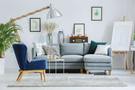 Blue armchair on grey carpet in designers living room with lamp, easel and grey sofa