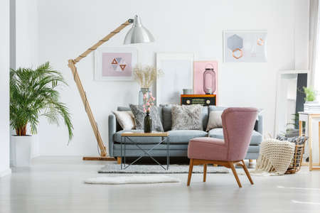 Beige blanket in basket on floor in living room with pink armchair and artistic posters on wall Banco de Imagens