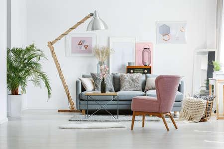 Beige deken in mand op vloer in woonkamer met roze leunstoel en artistieke affiches op muur