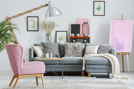 Roze leunstoel op grijs tapijt in woonkamer met witte deken op grijze bank en ontworpen lamp