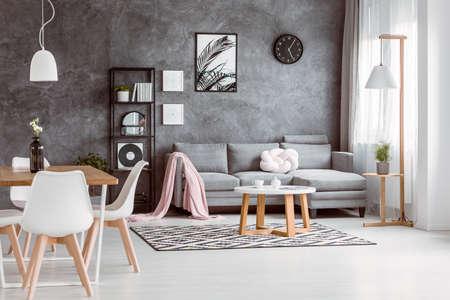 Lamp boven eettafel met zwarte vaas in ruime woonkamer met zwart en wit tapijt Stockfoto