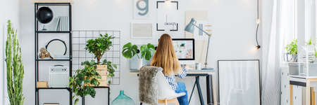 Panorama of girl sitting in trendy scandi room with posters on white wall, desk, computer, monstera plant and cactus