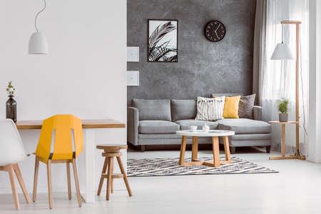 Gele stoel bij houten lijst in moderne woonkamer met decoratieve hoofdkussens op grijze bank