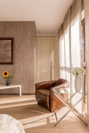 Brown vintage armchair, sunflower and white flowers in neutral colored room