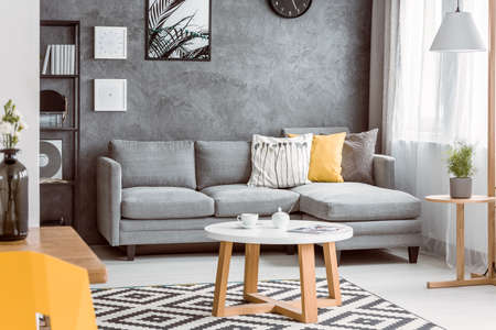 Wooden coffee table on black and white carpet in living room with yellow pillow on grey sofa Stock Photo - 84779039