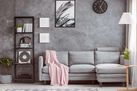 灰色の快適なコーナーソファ、床と暗い壁の黒い時計の小さなツリーとスタイリッシュなリビング ルーム