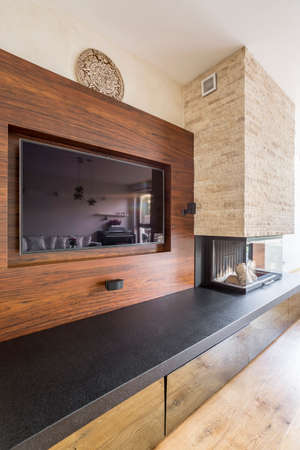 TV on wooden wall and fireplace with brick chimney in elegant room