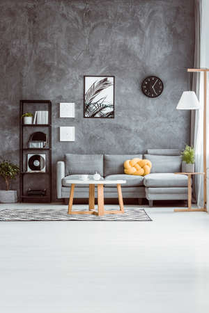 Spacious living room with coffee table on carpet in scandinavian style and grey sofa against concrete wall