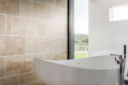 커다란 창문이있는 마당이 내려다 보이는 욕실의 아늑한 욕조