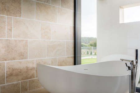 Cozy bathtub in a bathroom overlooking the yard with a giant window Banco de Imagens