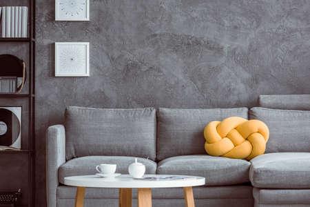 콘크리트 벽에 회색 settee에 노란색 베개와 거실에서 나무 커피 테이블에 흰색 컵