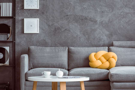 White cup on wooden coffee table in living room with yellow pillow on grey settee against concrete wall Foto de archivo
