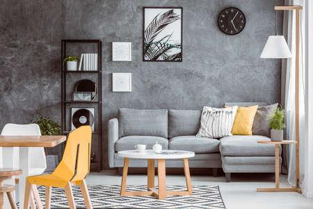 枕でセットグレーカウチの近くに木製の腰掛けにダイニングテーブルと植物を備えた多機能リビングルーム 写真素材