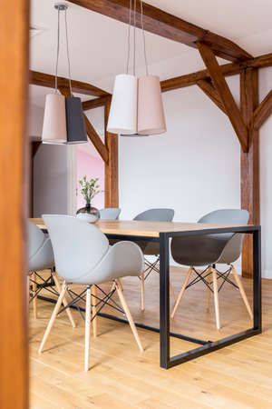 Designed lamps above dining table with grey chairs in spacious room with wooden construction 版權商用圖片