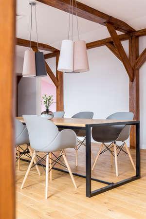 Gestaltete Lampen über Esstisch mit grauen Stühlen in großzügigem Raum mit Holzkonstruktion Standard-Bild - 84779187