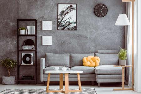 黒の時計と居心地の良いリビング ルームで黄色の枕と灰色の長いすの上の暗い壁の上にポスター 写真素材