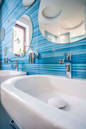 Simple sink in fun blue bathroom with bubble shaped mirrors