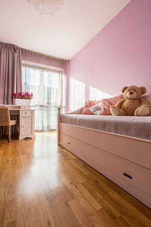 Lilac girly bedroom with elegant white furniture and teddy bear Stock Photo